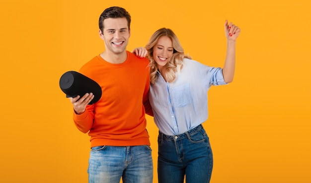 Schönes lächelndes junges paar, das drahtlosen lautsprecher hält, der musik hört, die emotionale bunte artglücksstimmung auf gelbem hintergrund tanzt