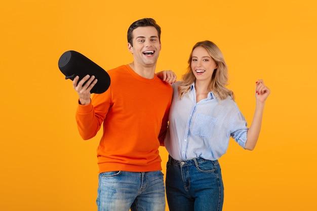 Schönes lächelndes junges paar, das drahtlosen lautsprecher hält, der musik hört, die emotionale bunte artglücksstimmung auf gelber wand tanzt
