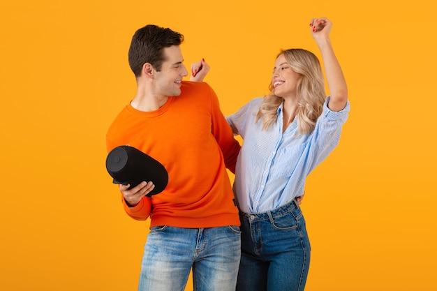Schönes lächelndes junges paar, das drahtlosen lautsprecher hält und musik tanzt emotional hört