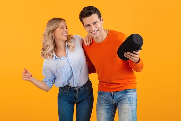 Schönes lächelndes junges paar, das einen drahtlosen lautsprecher hält und musik hört, die emotional isoliert auf gelb tanzt
