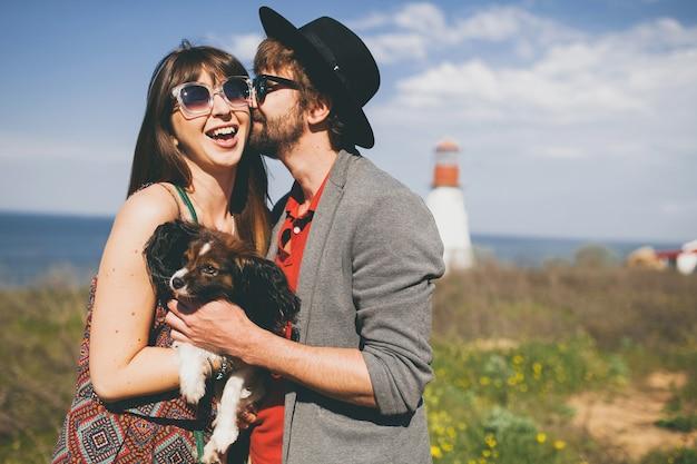 Schönes lächelndes junges stilvolles hipster-paar in der liebe, die mit hund in der landschaft geht