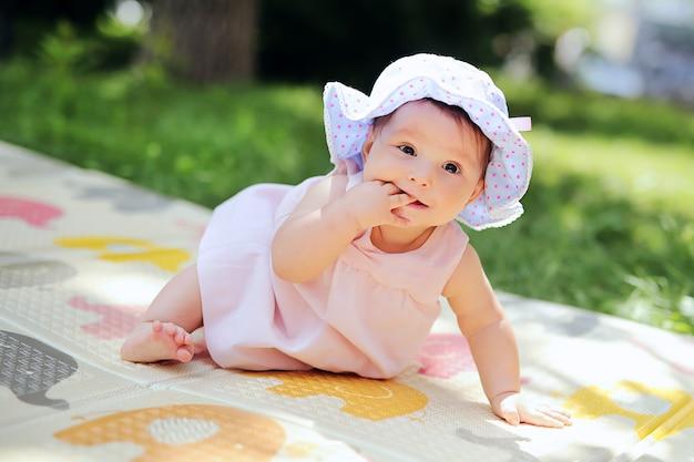 Schönes lächelndes kind, das im garten spielt. glückliches nettes kind, das spaß im park hat. süßes sonniges baby im panama-hut