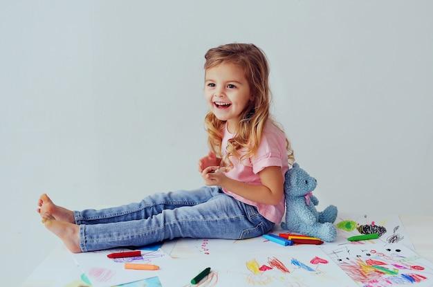 Schönes lächelndes kind des europäischen auftrittes sitzend auf zeichnungen der kinder. nettes kleines mädchen, das mit teddybären spielt