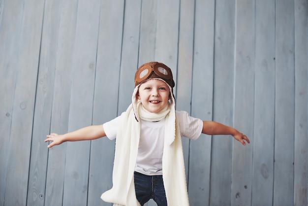 Schönes lächelndes kind im sturzhelm auf einem blauen hintergrund, der mit einem flugzeug spielt. oldtimer-pilot