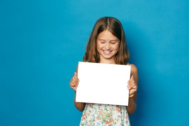 Schönes lächelndes kind (mädchen) mit weißen zähnen, die in händen weißen leeren kopienraum für die ankündigung halten