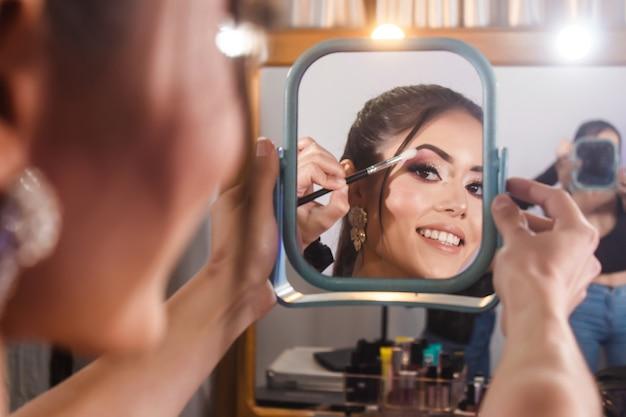 Schönes lächelndes mädchen, das einen spiegel hält, während der maskenbildner schatten auf ihren augen verschmiert.