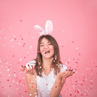 Schönes lächelndes mädchen, das konfetti in den händen lokalisiert über rosa hält