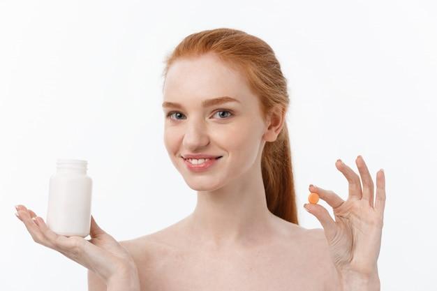 Schönes lächelndes mädchen, das medikamente nimmt und flasche mit pillen hält.