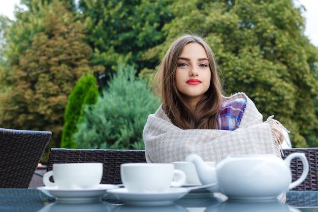 Schönes lächelndes mädchen, eingewickelt in eine decke, die am tisch in einem straßencafé sitzt