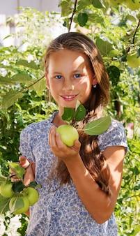Schönes lächelndes mädchen im garten mit grünen äpfeln, blaues kleid mit blumen