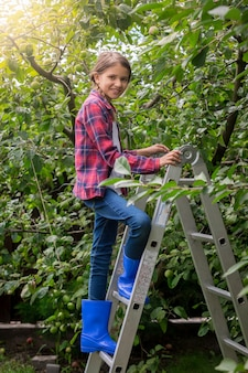 Schönes lächelndes mädchen im karierten hemd, das die trittleiter im obstgarten hochklettert