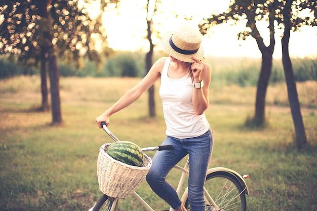 Schönes lächelndes mädchen im strohhut mit fahrrad im park