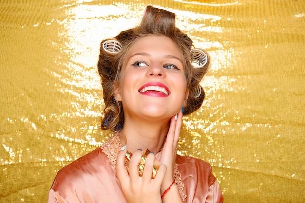 Schönes lächelndes mädchen in den lockenwicklern lokalisiert auf gold. porträt der jungen schönen sexy lächelnden frau. frau mit parfüm, junges schönes mädchen, das eine flasche parfüm hält und aroma riecht