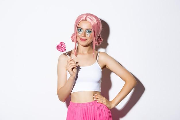 Schönes lächelndes mädchen in der rosa perücke, die herzförmige süßigkeit, süßes oder saures im märchenkostüm auf halloween, stehend hält.