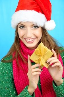Schönes lächelndes mädchen in weihnachtsmütze mit geschenk