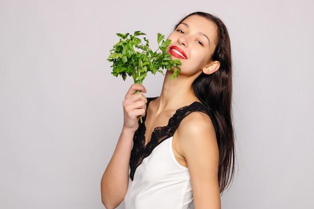 Schönes lächelndes mädchen mit petersilie. foto der modefrau auf grauem hintergrund. nahansicht. gesundes lebensstilkonzept. petersilie enthält viele vitamine.