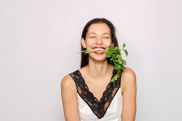 Schönes lächelndes mädchen mit petersilienfoto der modefrau auf grauem hintergrund