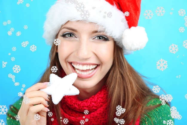 Schönes lächelndes mädchen mit weihnachtsschneeflocke auf blauer oberfläche
