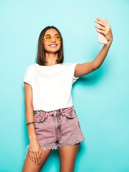 Schönes lächelndes modell gekleidet in sommer hipster kleidung. sexy sorgloses mädchen, das im studio nahe der blauen wand in den jeansshorts aufwirft. trendige und lustige frau, die selfie-selbstporträtfotos auf smartphone nimmt