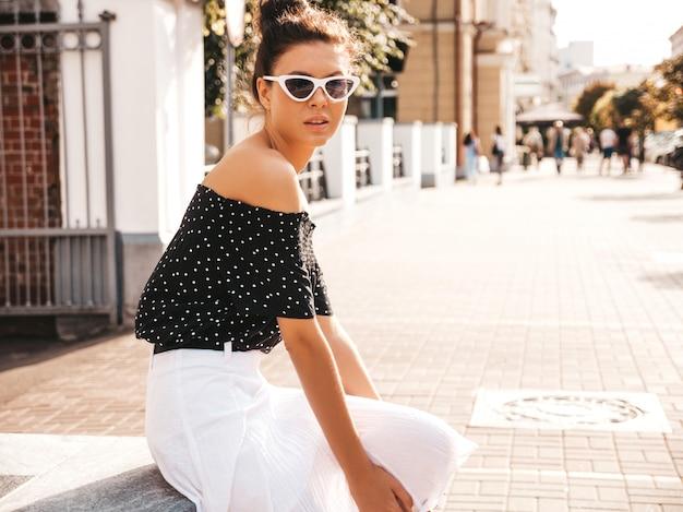 Schönes lächelndes modell kleidete in der eleganten sommerkleidung an sexy sorgloses mädchen, das in der straße sitzt trendy moderne geschäftsfrau in der sonnenbrille, die spaß hat