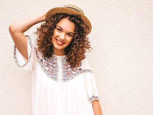Schönes lächelndes modell mit afrolockenfrisur kleidete im weißen kleid des sommerhippies an.