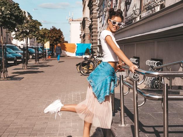Schönes lächelndes modell mit hörnerfrisur kleidete in der sommerhippie-jackenjeans-kleidung an sexy sorgloses mädchen, das in der straße aufwirft modische lustige und positive frau, die spaß in der sonnenbrille hat