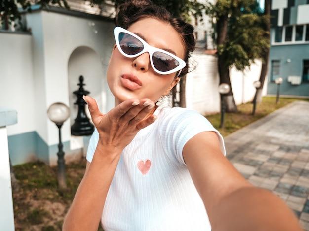 Schönes lächelndes modell mit hörnerfrisur kleidete in der zufälligen kleidung des sommers an sexy sorgloses mädchen, das in der straße in der sonnenbrille aufwirft machen von selfie selbstporträtfotos auf smartphone geben des luftkusses