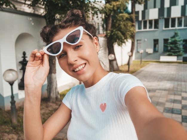 Schönes lächelndes modell mit hörnerfrisur kleidete in der zufälligen kleidung des sommers an sexy sorgloses mädchen, das in der straße in der sonnenbrille aufwirft machen von selfie selbstporträtfotos auf smartphone