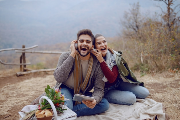 Schönes lächelndes multikulturelles paar in der liebe, die auf decke beim picknick im herbst sitzt, mit tablette und musik über kopfhörer hört. neben ihnen sind hund und korb mit futter.