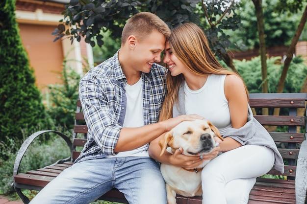 Schönes lächelndes paar, das an der bank mit ihrem hund sitzt. junge familie streichelt glücklichen labrador. mann und frau gehen den hund.