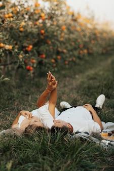 Schönes lächelndes paar, das picknicktag im apfelgarten genießt. sie liegen und halten sich an den händen.