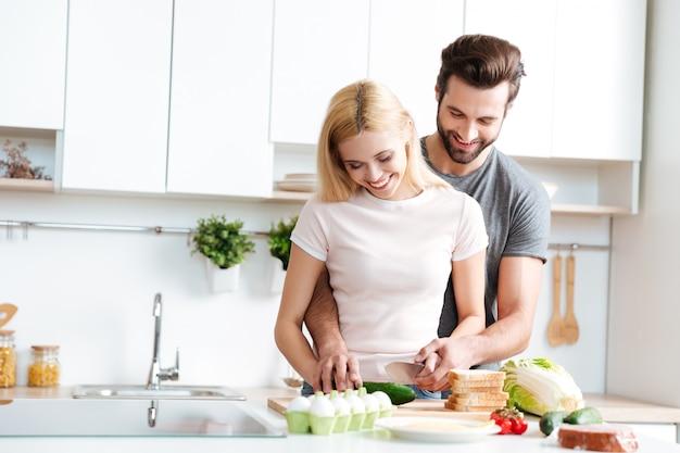 Schönes lächelndes paar, das zusammen in einer modernen küche kocht