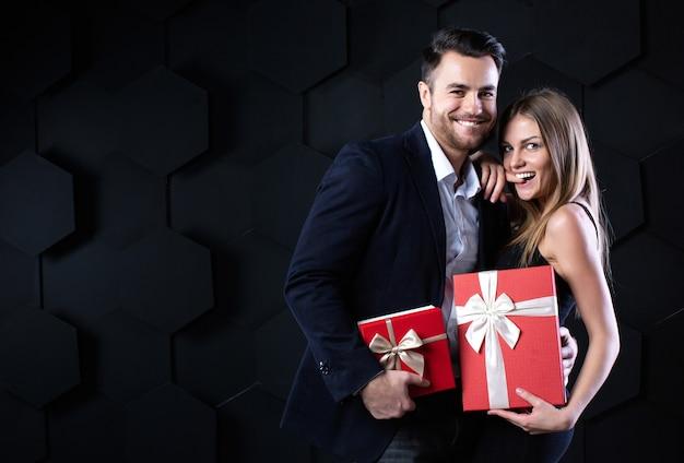 Schönes lächelndes paar mit geschenken. feier und romantisches konzept.