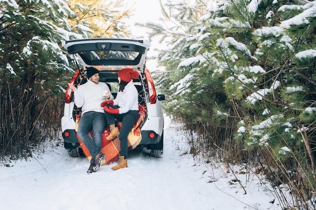 Schönes lächelndes paar sitzt im kofferraum im winterwald
