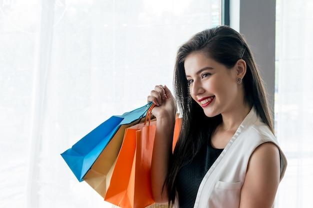Schönes lächelnmädchen, das bunte einkaufstasche hält