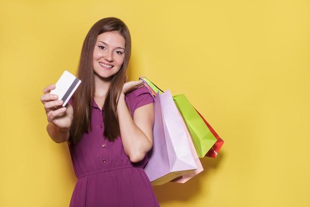 Schönes lässiges mädchen mit einkaufstasche, die ihr kreditauto zeigt