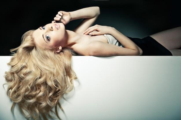 Schönes langes haar auf einer attraktiven frau über weißem brett
