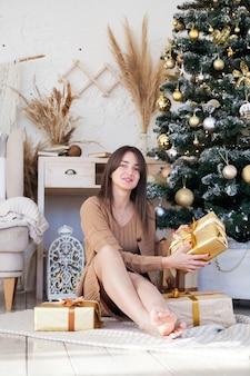 Schönes langhaariges mädchen nahe weihnachtsbaum, das goldene kisten mit geschenken hält und an kamera lächelt