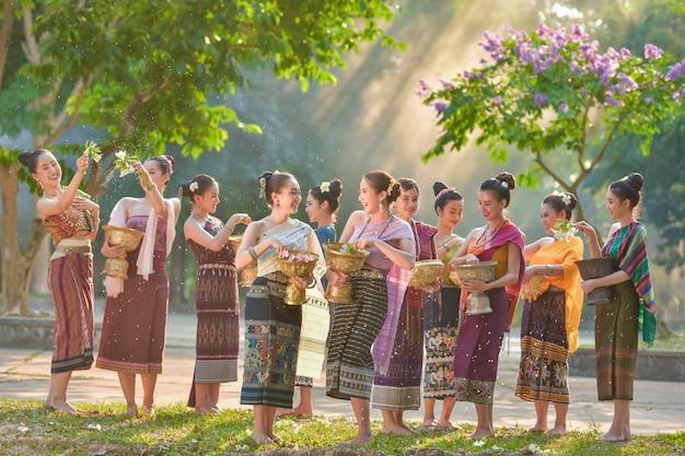 Schönes lao-mädchen im gebürtigen kleid spritzwasser während des traditionellen festivals lao vientiane