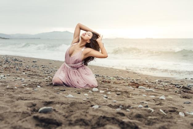 Schönes lateinisches mädchen mit dem langen schwarzen stock, das auf ihren knien auf einem wunderschönen sonnenuntergang am strand posiert, gekleidet in einem rosa ballettkleid
