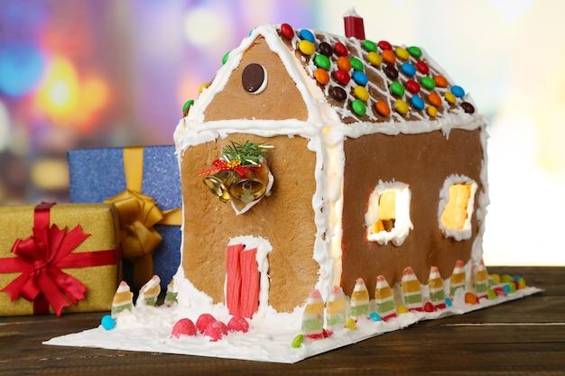 Schönes lebkuchenhaus mit weihnachtsdekor auf holztisch