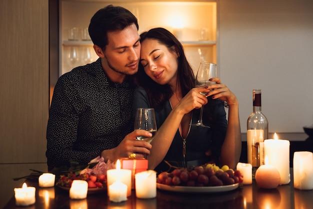 Schönes leidenschaftliches paar, das ein romantisches abendessen bei kerzenlicht zu hause hat, wein trinkt, röstet