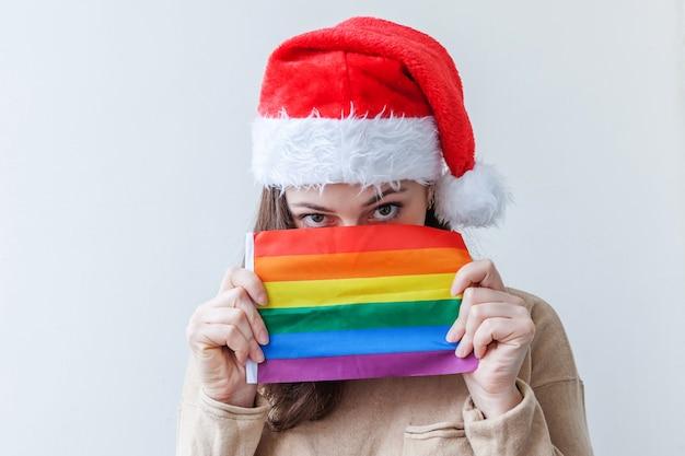 Schönes lesbisches mädchen im roten weihnachtsmannhut mit lgbt-regenbogenfahne lokalisiert auf weißem hintergrund