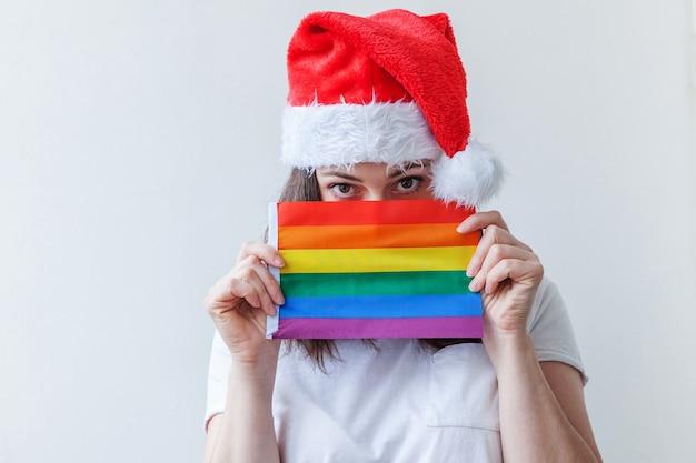 Schönes lesbisches mädchen im roten weihnachtsmannhut mit lgbt-regenbogenfahne lokalisiert