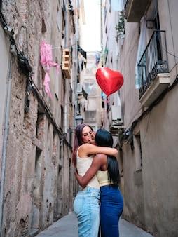 Schönes lesbisches paar, das sich umarmt, während es draußen auf der straße einen roten herzförmigen ballon hält. lgbt- und valentinstagskonzept.