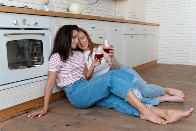Schönes lesbisches paar jubelt mit ein paar gläsern wein