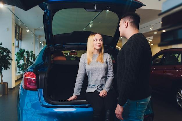 Schönes liebespaar, das in einem neuen auto zusammen am gutaussehenden mann des händlers und seiner liebenden freundin sitzt, die zusammen ein auto wählen