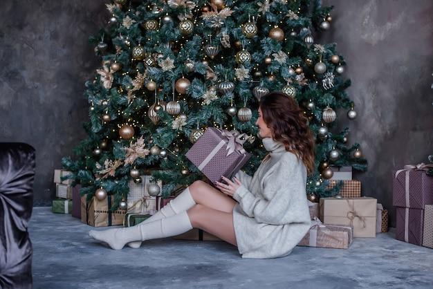 Schönes lockiges brünettes mädchen am weihnachtsbaum mit dekorationen