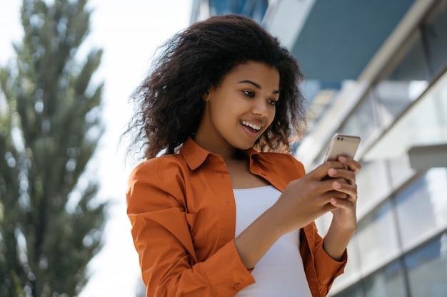 Schönes lockiges hipster-mädchen, das mobile app für online-shopping verwendet
