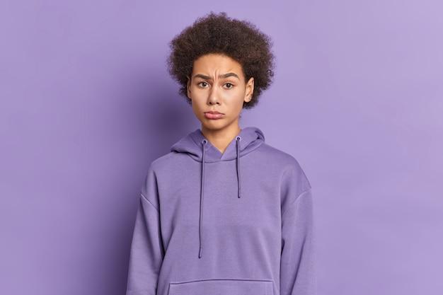 Schönes lockiges trauriges junges mädchen sieht unglücklich gekleidet im kapuzenpulli aus, der an jemandem beleidigt wird.